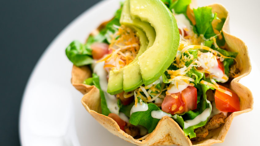 A taco salad in tortilla bowl is a fun and colorful way to eat mexican food. Made with fresh ingredients such as avocado, tomatoes, green salad, cheese and delicious greek yoghurt.